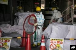 """Працівники атомної станції """"Фукушіма Даїчі"""" обприскують водою реактор після землетрусу 2011 року"""