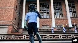 Una réplica de la estatua de Miguel Ángel David se encuentra afuera del Ayuntamiento de Montevideo vestido con la camiseta del equipo nacional de fútbol de Uruguay antes del comienzo de la transmisión televisiva del partido de la Copa Mundial Rusia 2018 entre Egipto y Uruguay