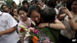 "A Chinese student is greeted by a relative after attending the end of the annual college entrance examinations, in Beijing, China, Tuesday, June 8, 2010. Each year, about 10 million high school seniors across China take the ""gaokao"" -- the exam that is th"