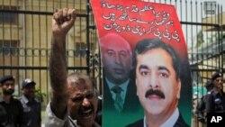 Một người ủng hộ đảng cầm quyền Pakistan cầm bức ảnh Thủ tướng Gilani trong cuộc biểu tình phản đối tòa án kết tội ông Gilani