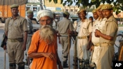 Indian security personnel stand guard as an elderly man walks past on September 29, 2010 in Ayodhya, on the eve of a court ruling that divided a long-contested holy site in the city between Hindus and Muslims (AFP).