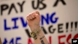 Seorang pekerja restoran cepat saji mengangkat tangannya dalam sebuah demonstrasi menuntut upah $15 per jam, di Empire State Plaza, Albany, New York (15/4).