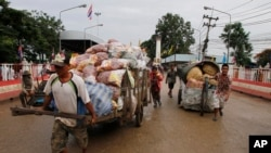 FILE PHOTO - Cambodian workers transport their goods brought from Thailand at a Cambodia-Thai international border gate in Poipet, Cambodia, Wednesday, June 18, 2014, for their daily business near the border between Cambodia and Thailand. (AP Photo/Heng S