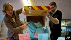 Nhân viên tại một địa điểm đầu phiếu ở Geneve, Thụy Sĩ, đổ thùng phiếu ra để kiểm sau cuộc trưng cầu dân ý. 9/2/14