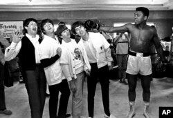 FILE - The Beatles, from left, Paul McCartney, John Lennon, Ringo Starr and George Harrison take a fake blow from Cassius Clay, who later changed his name to Muhammad Ali, while visiting the heavyweight contender in Miami Beach, Fla., Feb. 18, 1964.