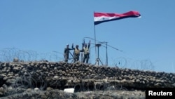 Syrian forces of President Bashar al Assad are seen celebrating on al-Haara hill in Quneitra area, Syria, July 17, 2018.