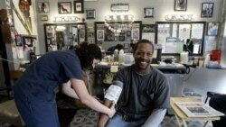 Dwight Woods has his blood pressure checked by Meghan Welsh at Flotrin's Barber Shop in St. Louis in this file photo
