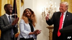 President Donald Trump, right, gives the thumbs up to Cam'eron Hill, left, and his mother LaSonya Hill, of Jacksonville, Fla., during an event about taxes, June 29, 2018, in the East Room of the White House in Washington.