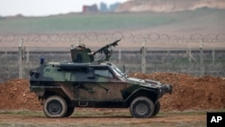 FILE - A Turkish military vehicle is seen patrolling the Turkey-Syrian border near the Akcakale border crossing in Turkey, January 2015.