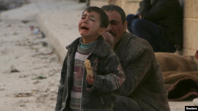 A boy cries at a site hit by what activists say was an airstrike by forces loyal to Syrian President Bashar al-Assad in Masaken Hanano in Aleppo, Feb. 14, 2014.