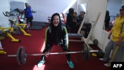 """In this photo, Afghanistan national power-lifting team member Rasheda Parhiz does an exercise called """"dead lift,"""" March 4, 2018. (AFP Photo)"""