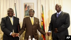 President Robert Mugabe, centre, shares a light moment with Morgan Tsvangirai, left, Zimbabwe's Prime Minister and his Deputy, Arthur Mutambara after giving their end of year message to the nation, at Zimbabwe House in Harare, Wednesday, Dec. 23, 2009. Th