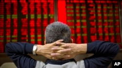 FILE - A Chinese investor watches stock prices at a brokerage house in Beijing, Sept. 16, 2015.