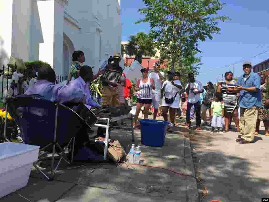 A group sings outside of Emanuel AME church in Charleston, South Carolina, June 21, 2015. (Amanda Scott/VOA)