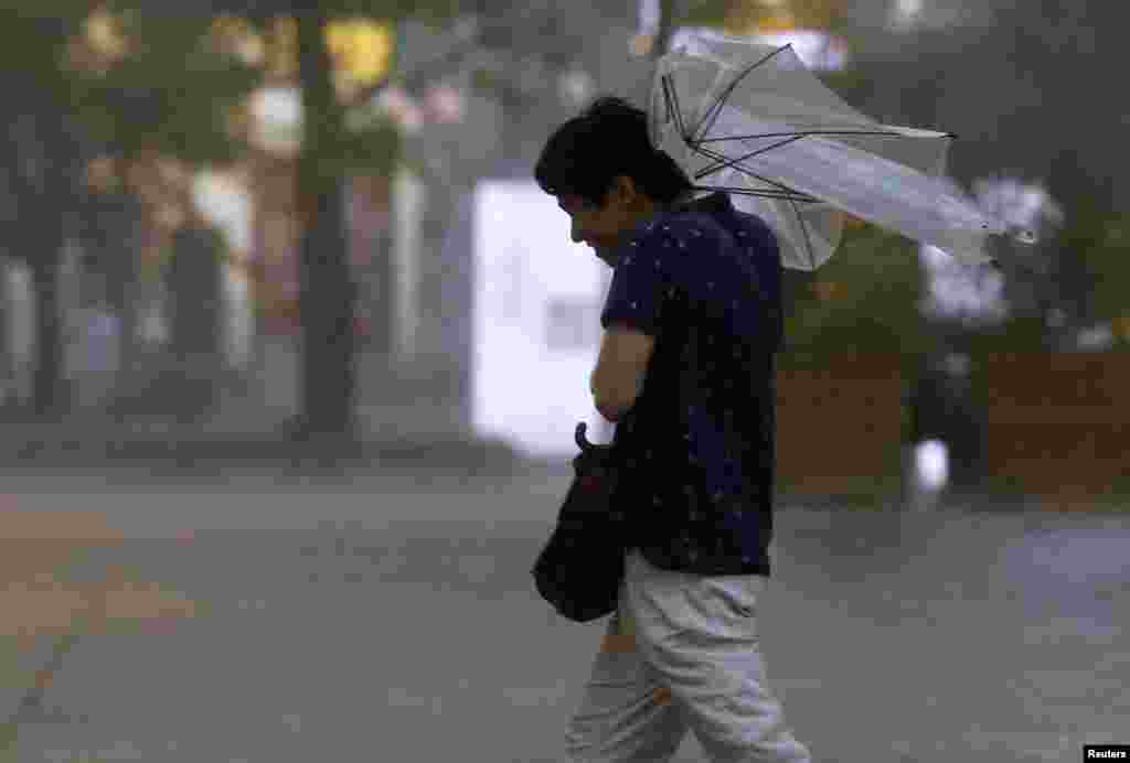 A man struggles with an umbrella in strong winds and rain caused by Typhoon Halong in Tokyo, Japan, Aug. 10, 2014.