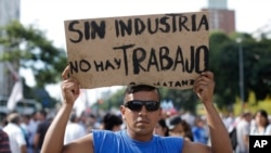 "A demonstrator holds a sign that reads in Spanish ""Without industry there is no work"" during a labor march in Buenos Aires, March 7, 2017."