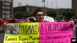 Seorang warga membentangkan pengumuman rincian terkait hilangnya kerabat mereka dalam aksi protes di Mexico City (30/5). 11 orang dilaporkan hilang diculik dari sebuah bar di ibukota Meksiko itu, hanya 20 hari pasca insiden tewasnya cucu pemimpin hak-hak sipil Malcolm X di wilayah itu.