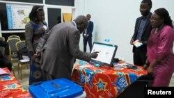 Un homme s'exerce à utiliser une machine à voter électronique lors d'une manifestation devant le siège de la commission électorale du Congo (CENI) à Gombe, dans la municipalité de Kinshasa, en RDCongo, le 1er mars 2018. EUTERS/Robert Carrubba - RC1DFD65E690
