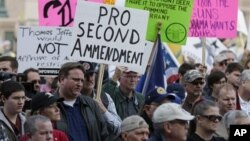 Para pendukung hak kepemilikan senjata membawa poster-poster berdemonstrasi di depan gedung DPRD Texas di Austin, hari Sabtu (19/1).
