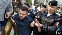 Police detain a demonstrator during a rally protesting retirement age hikes in Moscow, Russia, Sunday, Sept. 9, 2018. (AP Photo/Dmitry Serebryakov)
