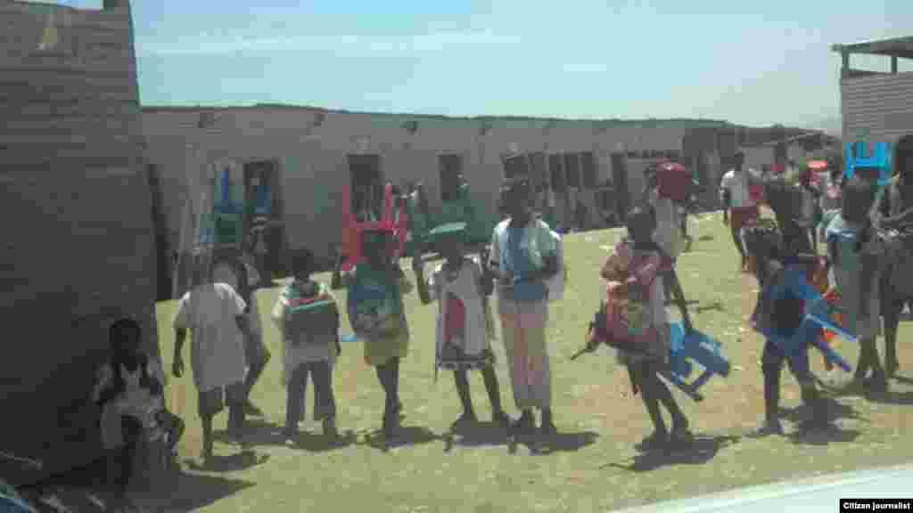 Os alunos levam as suas cadeiras para a escola. O olhar de um ouvinte da VOA pelo Ensino Primário, Escola 4, província de Benguela, Angola. Março 2014