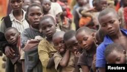 Des enfants réfugiés, déplacés par les conflits incessants dans la province du Nord-Kivu en RDC, attendent leur ration de nourriture à Nyakabande, un camp de transit de la ville de Kisoro en Ouganda, le 13 juillet 2012.