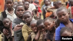 Refugee children, displaced by fighting in North Kivu Province in the Democratic Republic of Congo, wait for food in a transit camp in Kisoro town.