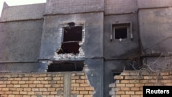 Men stand beside a damaged building near Mitiga airport in Libya's capital Tripoli, Nov. 25, 2014.