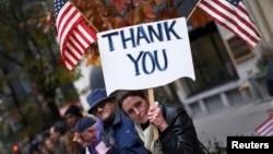 Una mujer muestra un cartel de agradecimiento durante un desfile en Nueva York por el Día de los Veteranos.