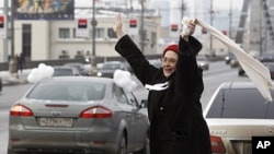 A woman greets participants of a car rally calling for a free presidential election, Moscow, February 19, 2012.