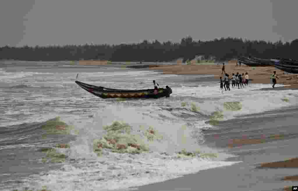 Fishermen pull out a boat as a cyclone approaches from the Bay of Bengal at Gokhurkuda, India, Oct. 11, 2013.