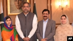 In this photo released by the Press Information Department, Pakistani Nobel Peace Prize winner Malala Yousafzai, left, and her parents stand for a photograph with Shahid Khaqan Abbasi, second from left, Prime Minister of Pakistan in Islamabad, Pakistan, Thursday, March 29, 2018. (Press Information Department via AP)