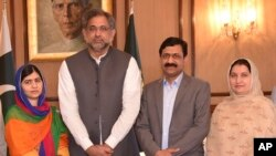 In this photo released by the Press Information Department, Pakistani Nobel Peace Prize winner Malala Yousafzai, left, and her parents pose for a photograph with Shahid Khaqan Abbasi, second from left, Prime Minister of Pakistan in Islamabad, Pakistan, Ma
