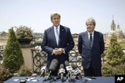 U.S. Secretary of State John Kerry, left, is flanked by Italian Foreign Minister Paolo Gentiloni, during a press conference that followed their meeting in Rome, Sunday, June 26, 2016.