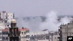 Ảnh trích từ một video nghiệp dư cho thấy khói bốc lên từ các tòa nhà trong thành phố Homs