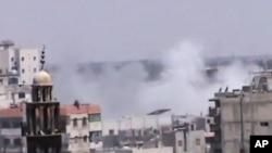 Ảnh chụp từ video cho thấy khói bốc lên gần một đền thờ Hồi giáo ở Homs, ngày 21/6/2012