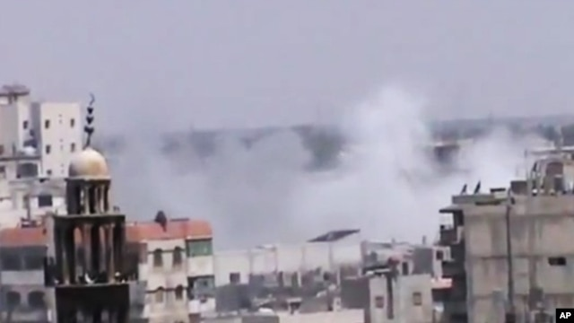 An amateur video released by the Shaam News Network purports to show smoke rising from buildings near a mosque in Homs, Syria, June 21, 2012.