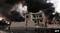Một người dân Iraq đi ngang qua một giếng dầu đang bốc khói nghi ngút, sau khi bị nhóm Nhà nước Hồi giáo đốt trên đường tháo chạy khỏi khu vực sản xuất dầu Qayyarah, ngày 30 tháng 08 năm 2016.