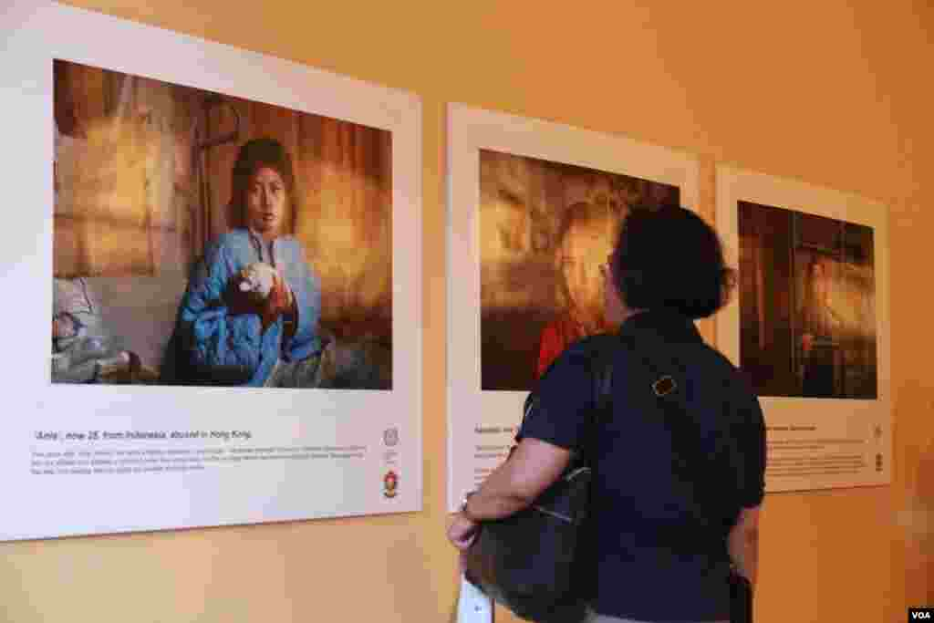 "Audience look at photos of victims from the abuse of domestic workers in an exhibition ""No one should work this way"" at Foreign Correspondent of Phnom Penh on May 7th 2015. (Nov Povleakhena/VOA Khmer)"