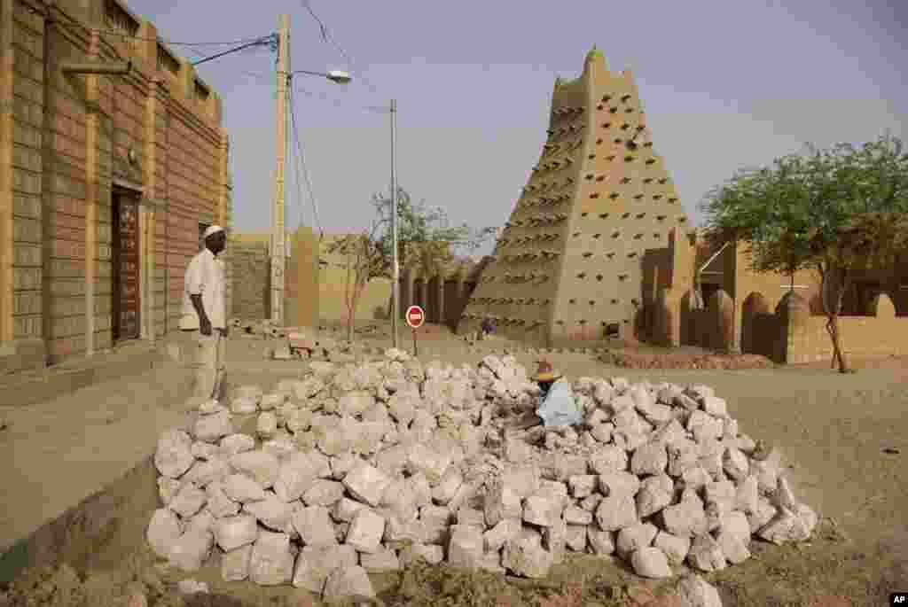 Des hommes travaillant près de l'une des mosquées historiques de Tombouctou.