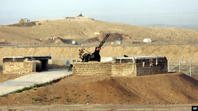 Nhân viên an ninh đứng cạnh một khẩu súng chống máy bay tại cơ sở làm giàu hạt nhân của Iran ở Natanz, 300km %28186 dặm%29 về phía nam thủ đô Tehran, Iran.