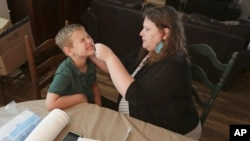 Mendy McNulty swabs the nose of her son, Andrew, 7, Tuesday, July 28, 2020, in their home in Mount Juliet, Tenn. (AP Photo/Mark Humphrey)