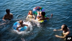 Children cool off on floating tube at Houhai Lake during summer heat in Beijing, July 28, 2013.