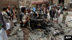 Yemenis surround the wreckage of a vehicle outside the Kobbat al-Mehdi Shi'ite mosque after a car bomb targeting the area killed two people in the capital Sana'a, June 20, 2015.