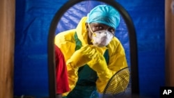 FILE - A health care worker dons protective gear before entering an Ebola treatment center in Freetown, Sierra Leone, Oct. 16, 2014.