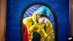 FILE - A health care worker dons protective gear before entering an Ebola treatment center in Freetown, Sierra Leone.