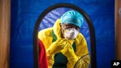Seorang petugas kesehatan memakai alat pelindung sebelum memasuki pusat perawatan Ebola di Freetown, Sierra Leone.