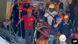 Rescuers carry an earthquake survivor after being pulled out from the rubble of a commercial building following a 6.1 magnitude earthquake in Porac township, Pampanga province, north of Manila, Philippines, April 23, 2019.