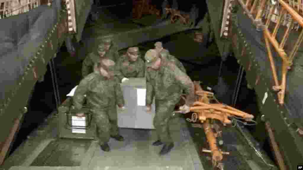 Des soldats russes tranportent des munitions dans un avion militaire à Hemeimeem sur une base aérienne en Syrie, le 15 mars 2016.