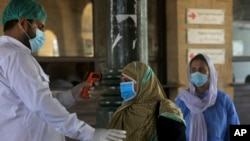د پاکستان په کراچي ښار کې د رېلوې یو کارکن د یوې رارسېدلې مسافرې د وجود حرارت ټېسټ کوي